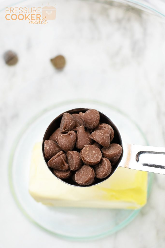 chocolate chips in a measuring cup over a bowl of butter