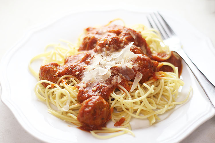 Easy Instant Pot Spaghetti & Meatballs with shaved parmesan on a white plate with a fork