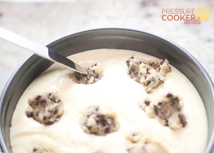 pressing cookie dough into Instant Pot Chocolate Chip Cookie Dough Cheesecake batter in springform pan