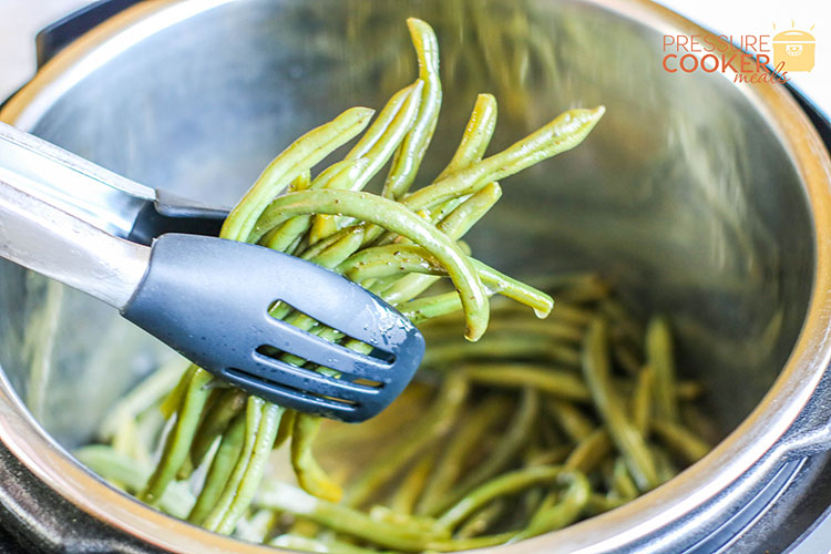 Instant Pot Southern Green Beans with bacon and onion being dipped from pot